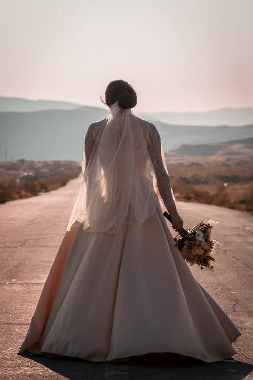 Woman in White Wedding Dress Standing on Brown Sand