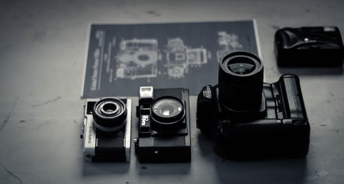 Retro photo cameras arranged on table