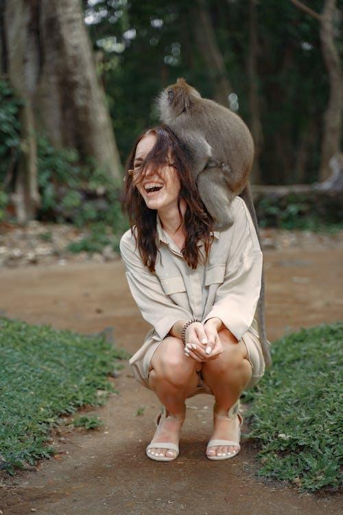 Cheerful woman having monkey on shoulder
