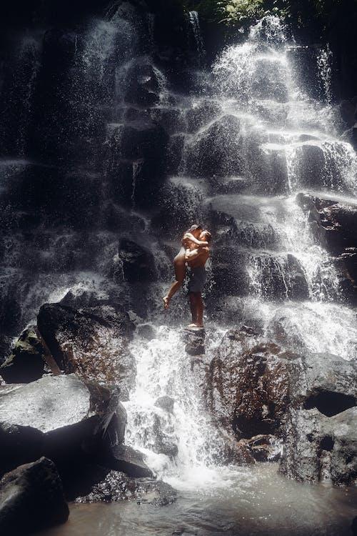 Couple kissing near waterfall on rock