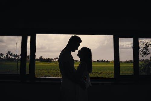 Unrecognizable couple embracing near window