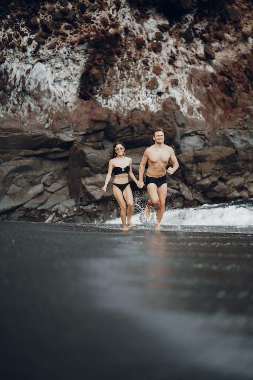 Happy couple running along seashn water