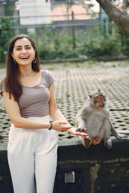 Laughing woman showing on monkey in park