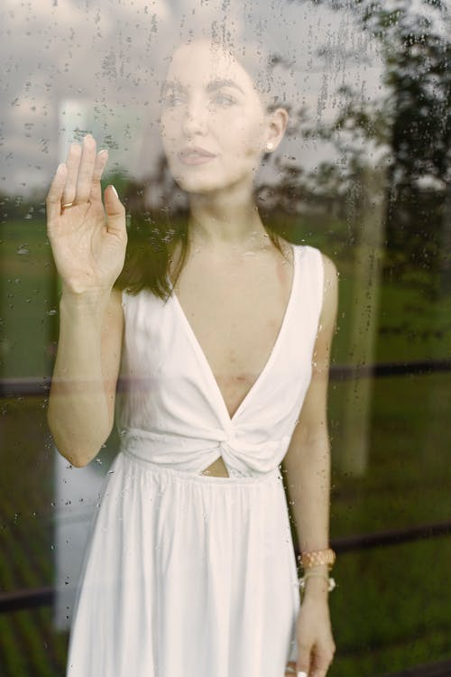 Through glass with drops of young female in white dress standing inside touching window in rainy weather in front of field