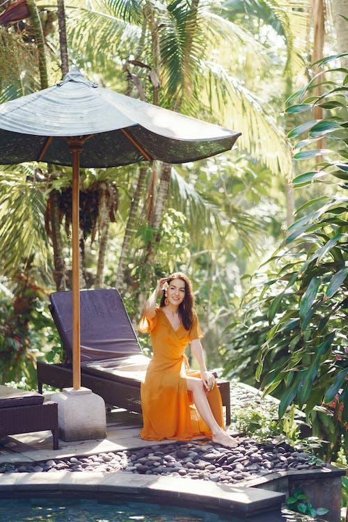 Young woman enjoying summer day in tropical garden
