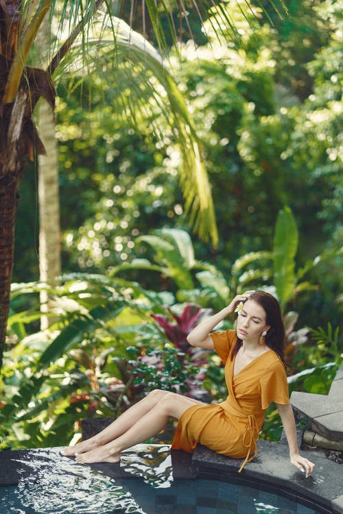 Relaxed woman resting on poolside in tropical resort