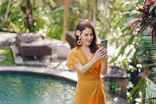 Cheerful woman taking photo of exotic plants