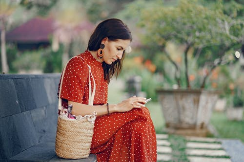 Calm woman in red dress using smartphone on bench