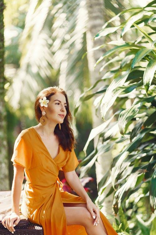 Content woman in summer dress resting in tropical garden