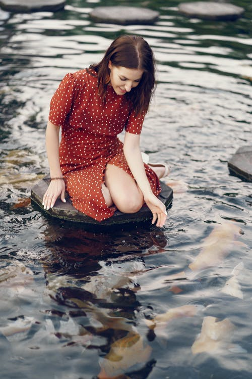 Woman in Red and White Polka Dot Dress Sitting on Water
