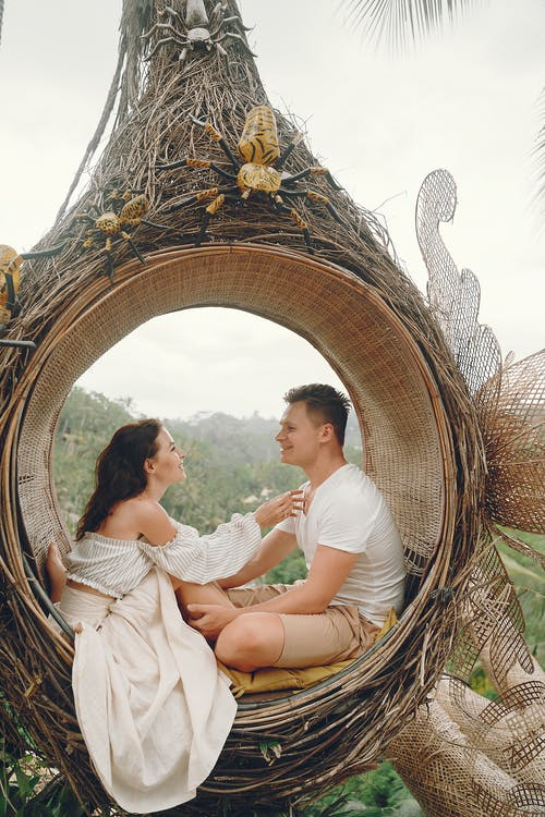 Happy couple resting in wicker hanging swing