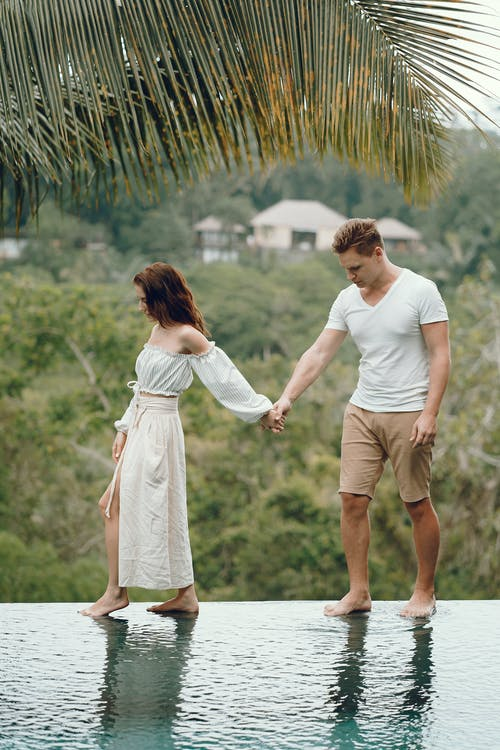 Full body barefoot anonymous stylish couple holding hands and standing on pool edge against scenic tropical countryside during romantic holidays