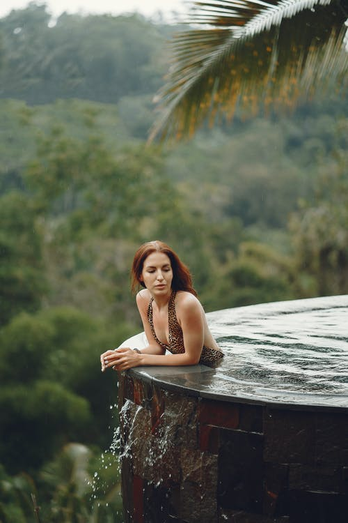 Positive content young female in trendy swimwear chilling in swimming pool with epic view of tropical jungle and looking away in daytime