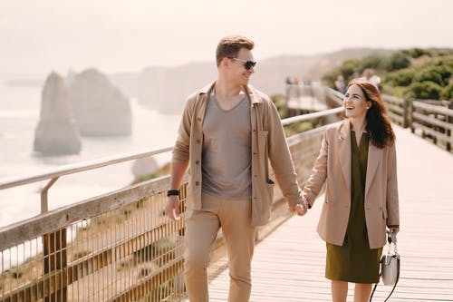 Man and Woman Walking on Bridge