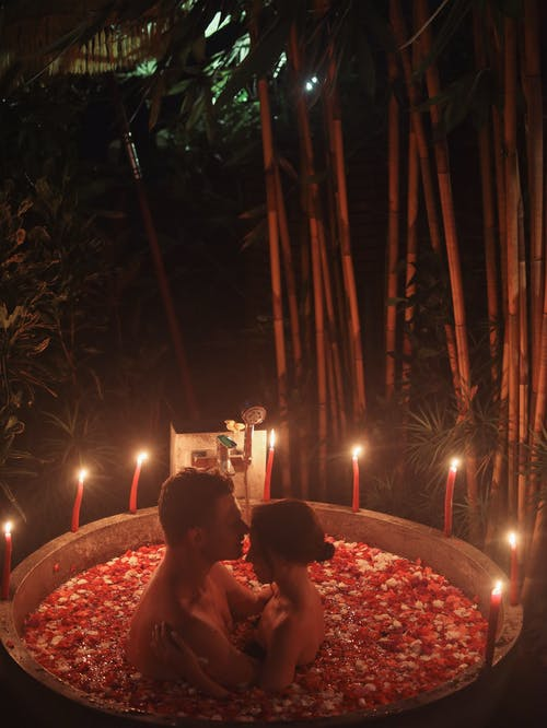 Alluring couple in bath with rose petals and candles