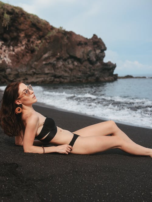 Relaxed woman resting on black sand beach
