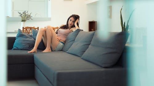 Full body of unemotional young female in casual clothing touching hair while chilling on sofa in bright room decorated with plants