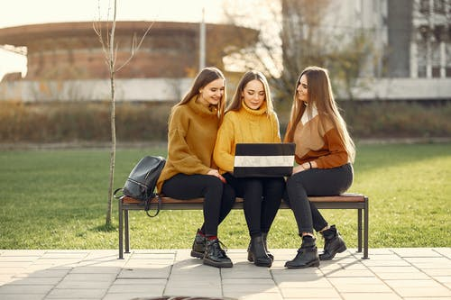 Positive girlfriends using laptop on bench