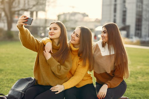 Cheerful girlfriends taking selfie on smartphone in park