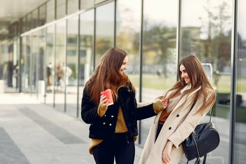 Best girlfriends having fun while standing against glass building