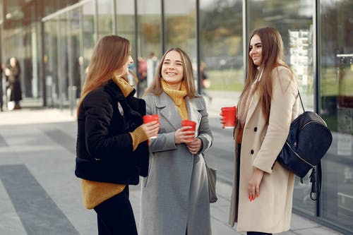 Beautiful female students standing near glass building while having friendly conversation outdoors