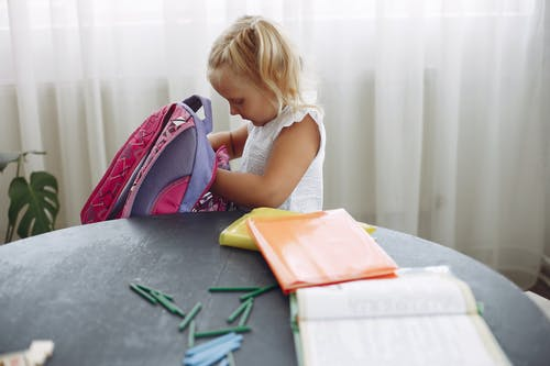 Concentrated girl searching pencil in backpack