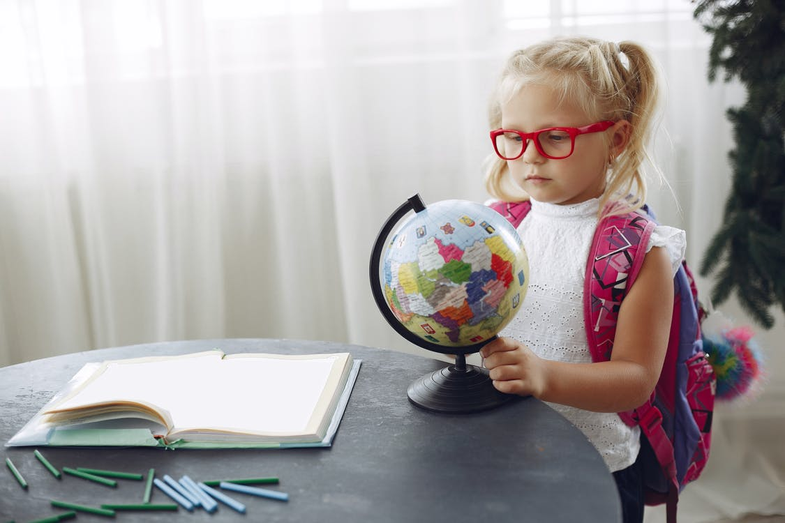 Little girl studying globe at home