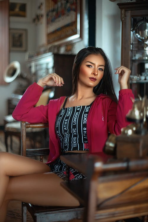 Woman in Red Blazer Sitting on Brown Wooden Chair