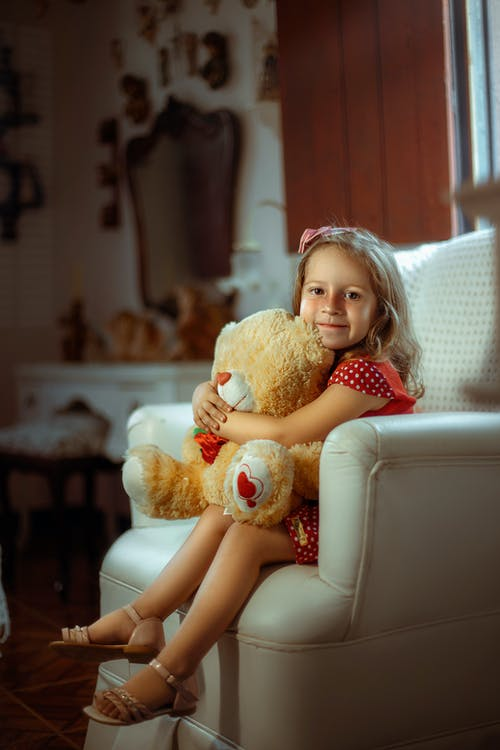 Girl in Red and White Polka Dot Dress Holding Brown Teddy Bear