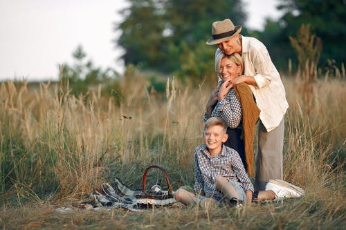 Happy LGBT family resting together in field