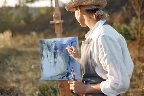 Anonymous woman in hat painting in field