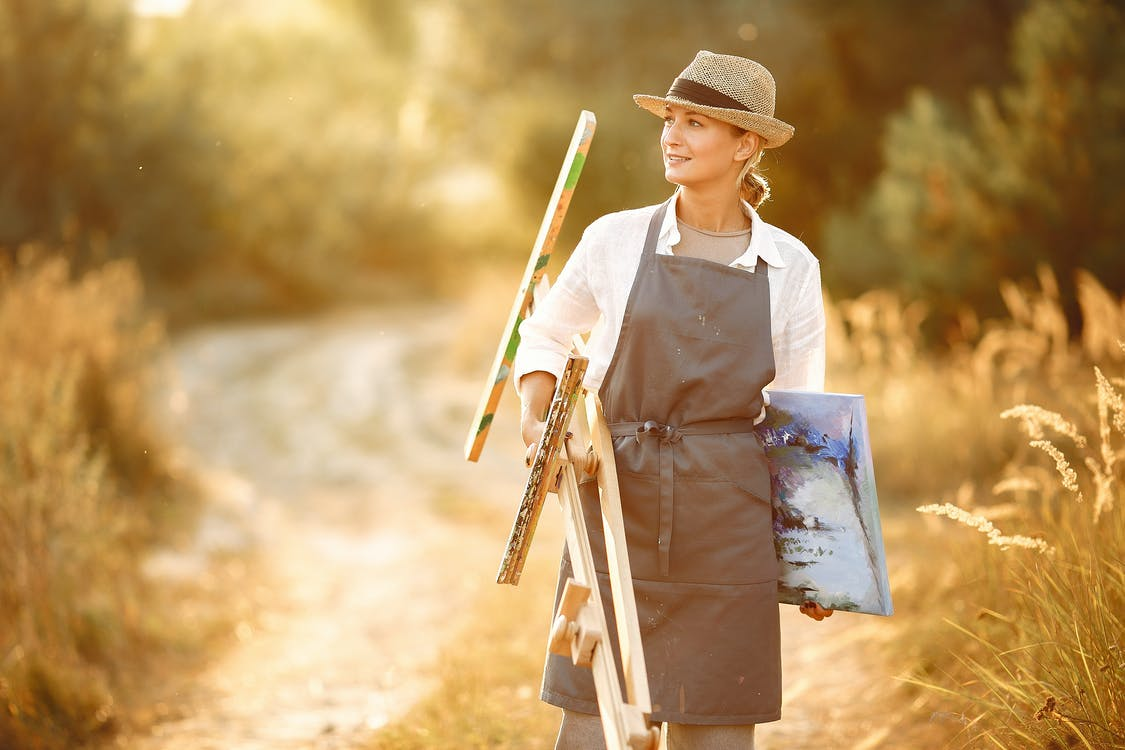 Happy female in hat and apron carrying easel and canvas while walking on road in summer sunny day in nature