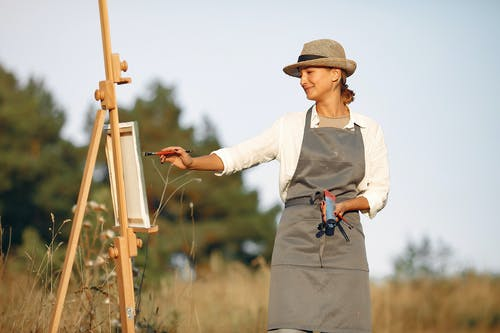 Happy woman in hat painting on canvas in field
