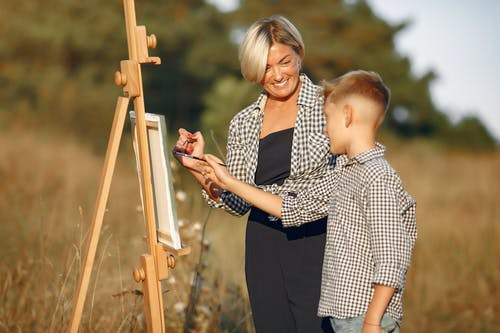 Cheerful woman with boy in casual clothes drawing on canvas while standing in summer sunny day on middle of field