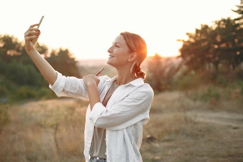 Happy woman taking selfie in nature