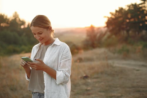 Happy woman using mobile phone in field