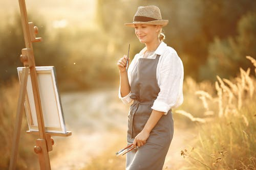 Side view of cheerful woman in hat and apron smiling and looking at own painting while standing in summer sunny day in nature