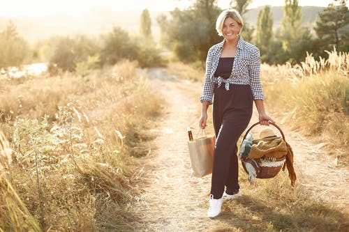 Happy woman walking with basket in countryside