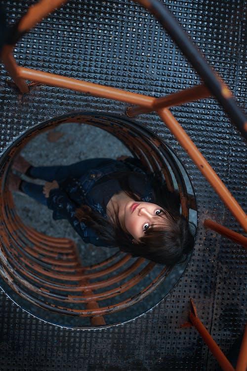 Girl in Black Jacket Lying on Brown Metal Spiral Stairs