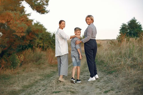 Back view of delighted adult mother and preteen son strolling together with middle age grandmother on path in summer field during weekend in countryside while looking over shoulder