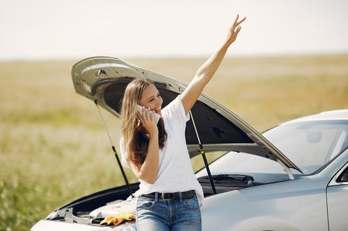 Positive woman using smartphone near broken automobile in countryside during car travel
