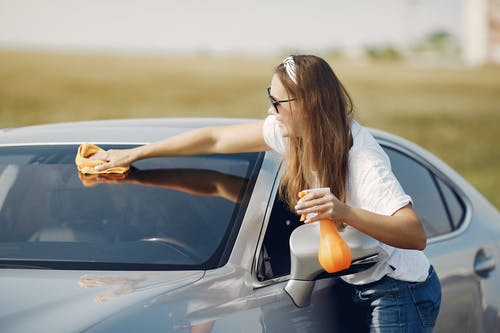 Smiling young woman wiping automobile in countryside during car travel