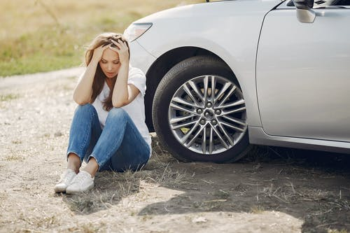 Frustrated female driver in white t shirt and jeans sitting on ground near damaged car with hands on head during car travel in sunny summer day