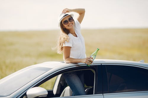 Cheerful young woman with refreshing drink in automobile during car trip