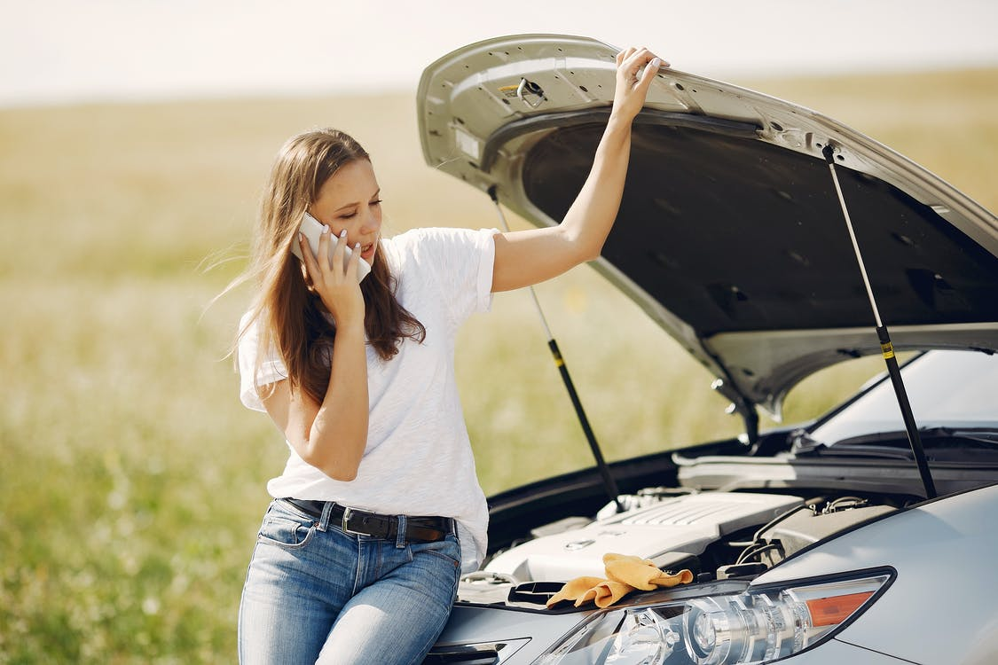 Upset woman using smartphone near broken automobile in countryside during car trip