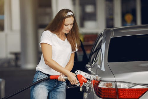 Attentive female driver in casual outfit and headband filling up modern automobile with automotive fuel gun on petrol station while looking down