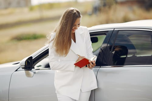Cheerful businesswoman taking notes during car travel