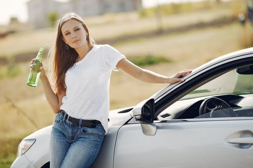 Content young woman with refreshing drink near modern automobile during car trip