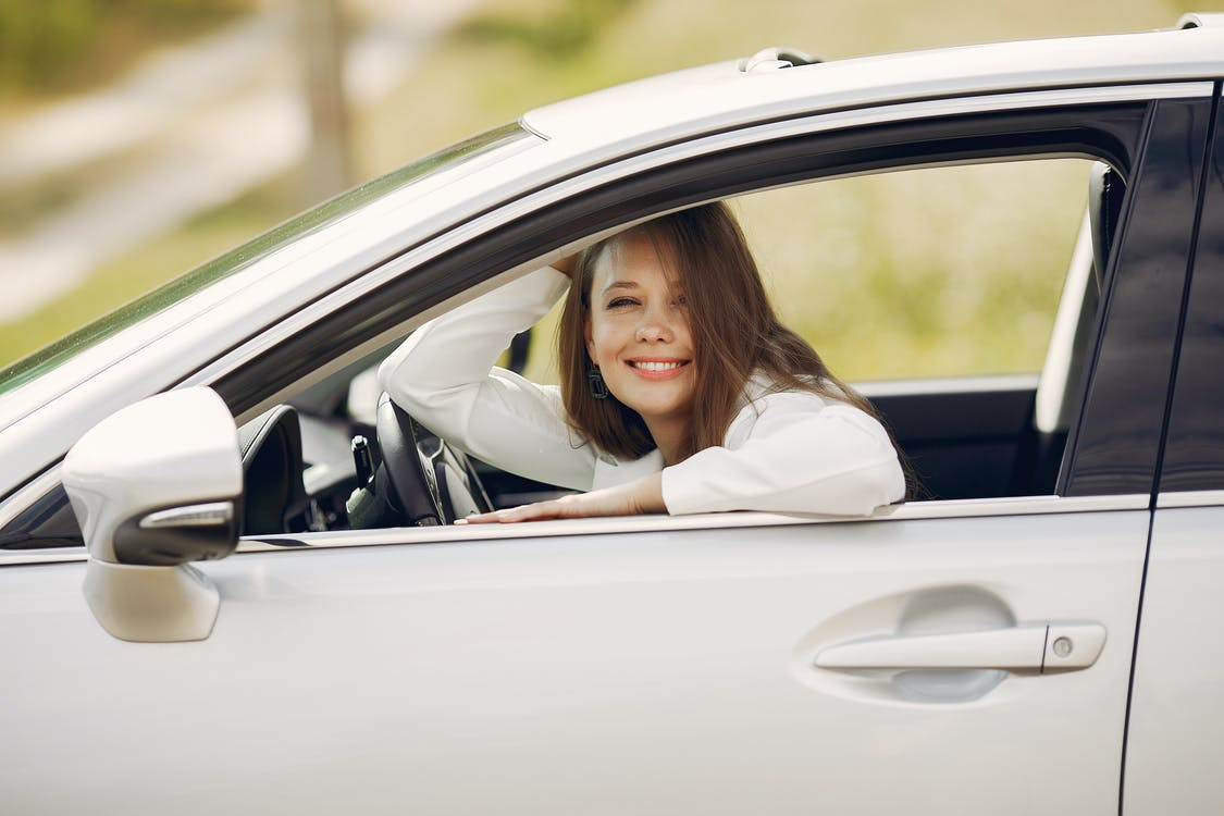 Cheerful female driver in white shirt sitting inside modern automobile and looking at camera through opened side window with smile during car trip in summer day