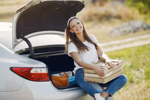 Cheerful female traveler in headband and casual clothes sitting in open trunk of car with wooden box while spending summer weekend in countryside and smiling looking away